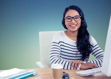 Усмехаясь женщина сидя на столе компьютера стоковые изображения rf