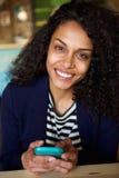 Усмехаясь женщина сидя на таблице кафа с мобильным телефоном Стоковое Изображение