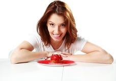 Усмехаясь женщина сидя на таблице с свежей клубникой испечет стоковые фото