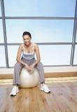 Усмехаясь женщина сидя на шарике тренировки Стоковая Фотография RF