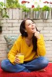 Усмехаясь женщина сидя с стеклянным апельсиновым соком Стоковые Изображения