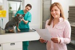 Усмехаясь женщина смотря Билл в ветеринарной хирургии Стоковая Фотография RF