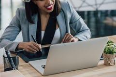Усмехаясь женщина смотря компьтер-книжку пока использующ графическую таблетку Стоковое Фото