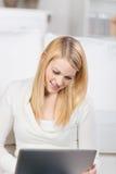 Усмехаясь женщина смотря компьтер-книжку сидя на софе Стоковые Фотографии RF