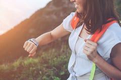 Усмехаясь женщина смотря умные вахты на ее запястье руки, пока trekking и идущ вдоль лугов горы Стоковое Фото