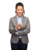 Усмехаясь женщина смотря smartphone стоковая фотография