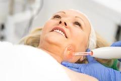 Усмехаясь женщина спа имея обработку на ее стороне имеет ослабить в центре здоровья стоковое изображение