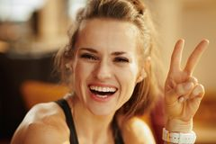 Усмехаясь женщина спорт в современной победе показа живущей комнаты стоковое фото rf