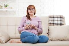 Усмехаясь женщина среднего возраста сидя на софе и печатая сообщении на умном телефоне дома Домохозяйка используя онлайн покупки  стоковые изображения