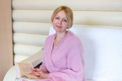 Усмехаясь женщина среднего возраста читая книгу дома стоковые фотографии rf