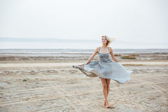 Усмехаясь женщина стоя и завихряясь на пляже Стоковое Изображение
