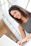 Усмехаясь женщина студента работая на компьтер-книжке Стоковое Фото