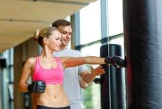Усмехаясь женщина с личным боксом тренера в спортзале стоковое изображение rf