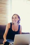 Усмехаясь женщина с короткими волосами на компьтер-книжке таблицы Стоковая Фотография