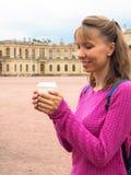 Усмехаясь женщина с кофе в бумажном стаканчике на предпосылке архитектурноакустических привлекательностей стоковая фотография