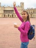 Усмехаясь женщина с кофе в бумажном стаканчике на предпосылке архитектурноакустических привлекательностей стоковые фото