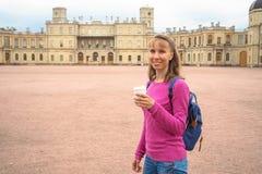 Усмехаясь женщина с кофе в бумажном стаканчике на предпосылке архитектурноакустических привлекательностей стоковые изображения
