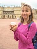 Усмехаясь женщина с кофе в бумажном стаканчике на предпосылке архитектурноакустических привлекательностей стоковые фотографии rf