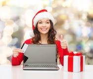 Усмехаясь женщина с кредитной карточкой и компьтер-книжкой Стоковые Изображения