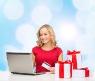 Усмехаясь женщина с кредитной карточкой и компьтер-книжкой Стоковые Фото
