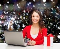 Усмехаясь женщина с кредитной карточкой и компьтер-книжкой Стоковая Фотография