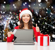 Усмехаясь женщина с кредитной карточкой и компьтер-книжкой Стоковое фото RF