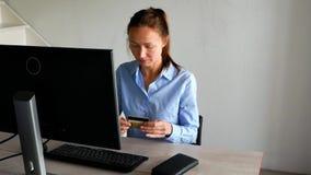 Усмехаясь женщина с ноутбуком и кредитной карточкой дома Девушка с картой ноутбука и банка внутри помещения акции видеоматериалы
