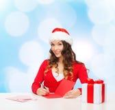 Усмехаясь женщина с письмом сочинительства подарочной коробки Стоковые Фото