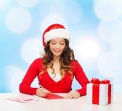 Усмехаясь женщина с письмом сочинительства подарочной коробки Стоковая Фотография RF