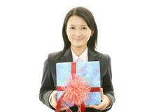 Усмехаясь женщина с подарком стоковые фото