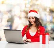 Усмехаясь женщина с подарочной коробкой и компьтер-книжкой Стоковое Изображение