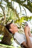 Усмехаясь женщина слушая к музыке на гамаке outdoors Стоковые Изображения RF