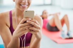 Усмехаясь женщина слушая к музыке на спортзале Стоковое фото RF