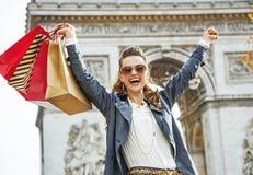 Усмехаясь женщина с хозяйственными сумками в ликование Париже, Франции стоковое изображение