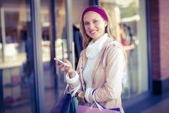 Усмехаясь женщина с хозяйственными сумками используя smartphone Стоковые Фото