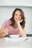 Усмехаясь женщина с шаром хлопьев читая газету в кухне Стоковые Фото