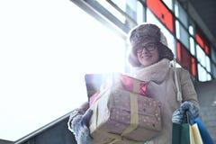 Усмехаясь женщина с штабелированными подарками и ходя по магазинам готовя окном во время зимы Стоковые Фотографии RF