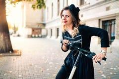 Усмехаясь женщина с электрическим самокатом пинком на красивый день осени стоковое изображение