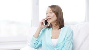 Усмехаясь женщина с smartphone дома акции видеоматериалы