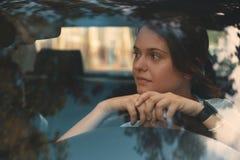 Усмехаясь женщина управляя автомобилем, привлекательной девушкой сидя в автомобиле стоковое изображение