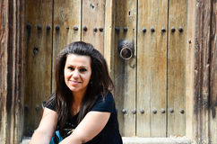Усмехаясь женщина усаженная перед старой дверью Стоковое фото RF