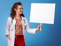 Усмехаясь женщина paediatrician смотря плакат на сини Стоковые Фотографии RF