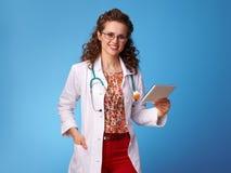 Усмехаясь женщина pediatrist используя ПК таблетки на сини Стоковые Изображения RF