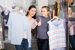 2 усмехаясь женщины выбирая одежды спать Стоковая Фотография RF
