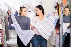 Усмехаясь женщины выбирая одежды спать Стоковая Фотография RF