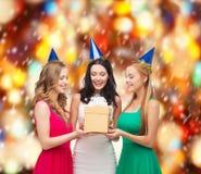 3 усмехаясь женщины в голубых шляпах с подарочной коробкой Стоковые Изображения