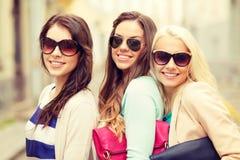 3 усмехаясь женщины в солнечных очках с сумками Стоковая Фотография