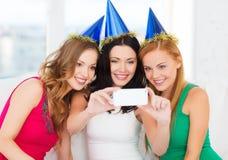 3 усмехаясь женщины в шляпах имея потеху с камерой Стоковые Фото
