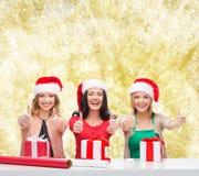 Усмехаясь женщины в шляпах хелпера santa пакуя подарки Стоковое Фото