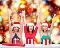 Усмехаясь женщины в шляпах хелпера santa с подарочными коробками Стоковое Изображение